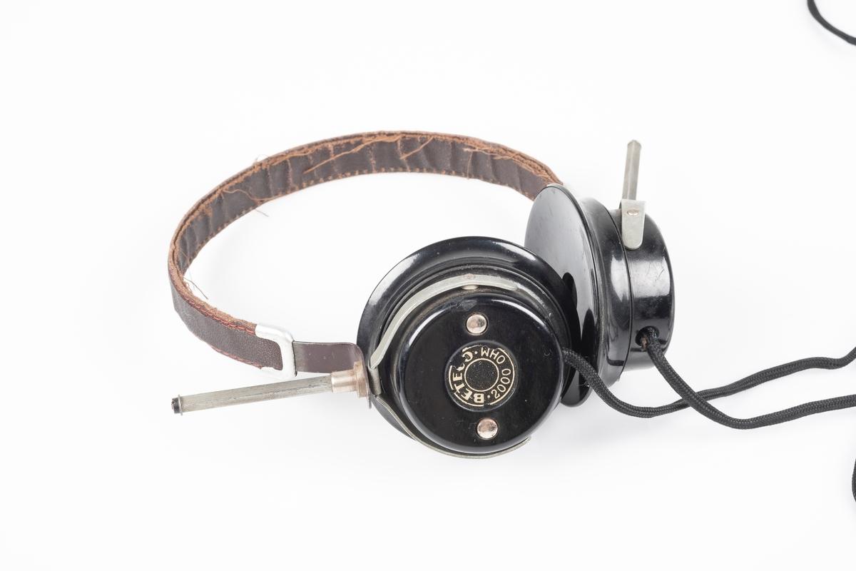 Hodetelefoner med svarte høyttalerelement i plast og bøyle i metall kledd av tekstil. Fra høyttalerelementene er det ledninger med to plugger i enden. Høyttalerelementene kan reguleres.