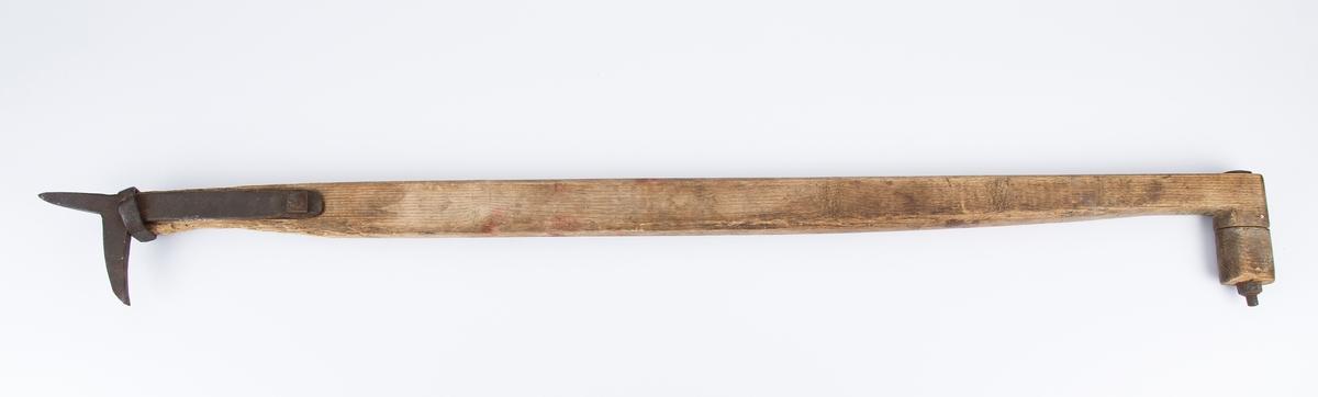Trestav med håndtak i den ene enden og jernpigg i den andre.