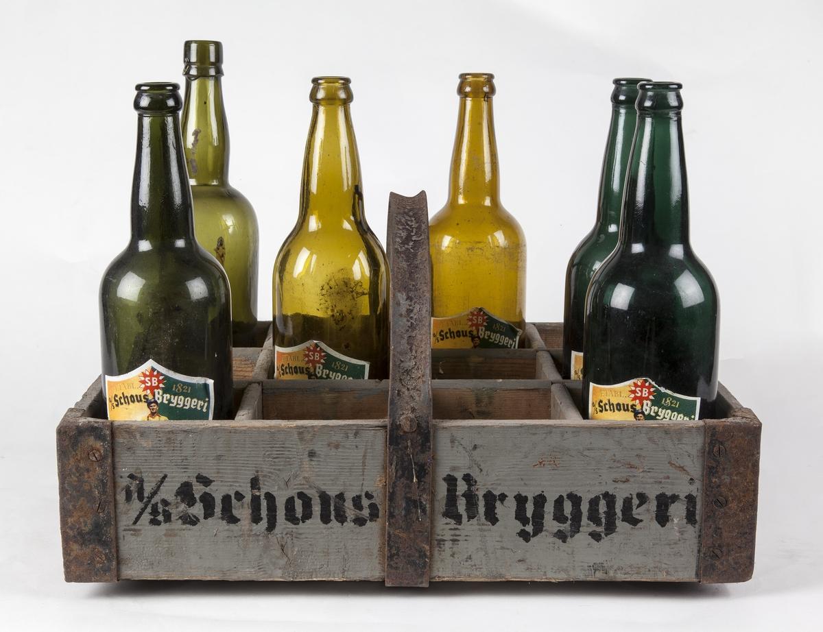 Ølkasse fra Schous bryggeri. Jernhank og jernbånd i bunn og hjørner. Sjablonmalt tekst.