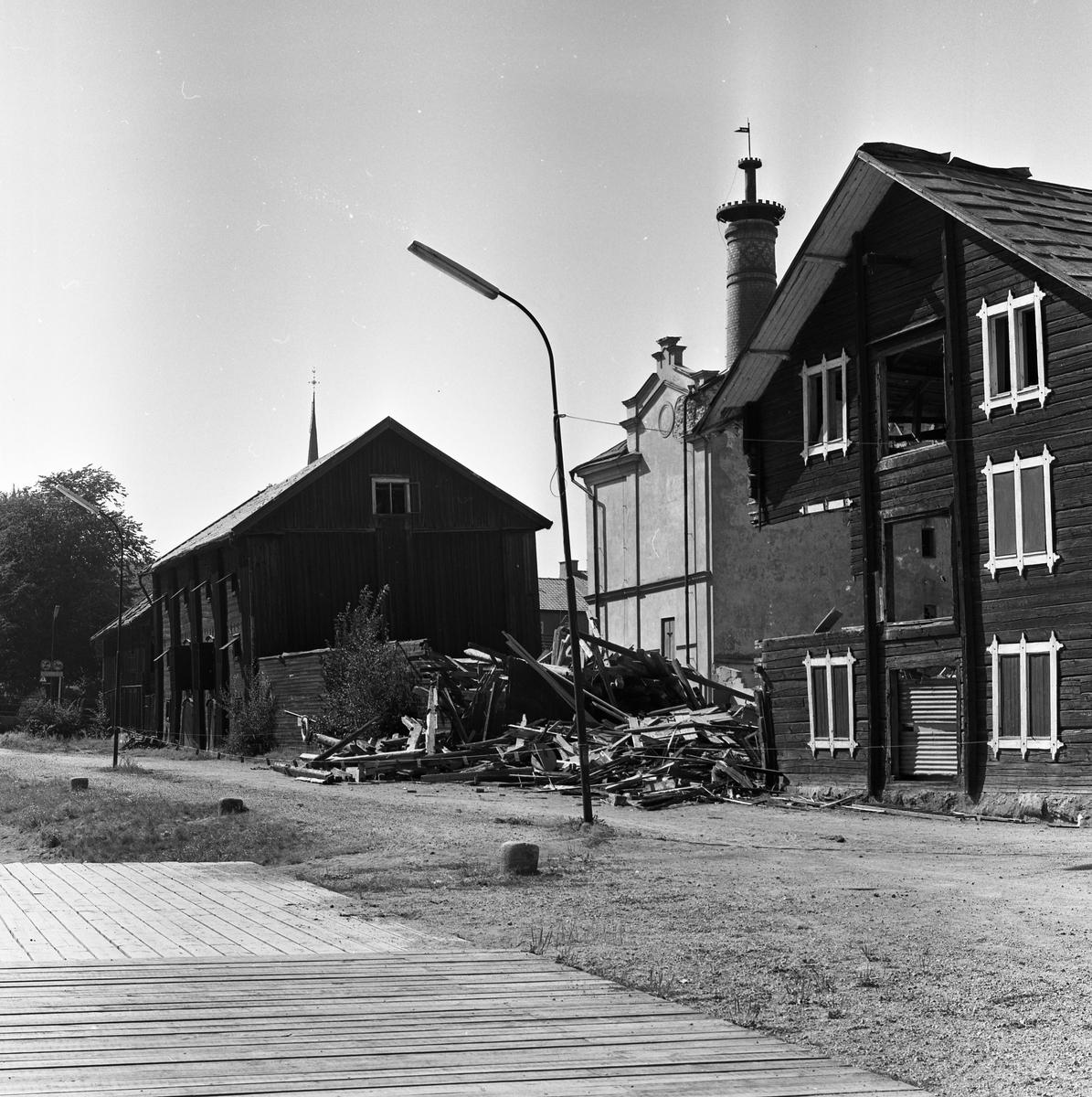 Arboga Kvarn och Maltfabrik har lagts ner. Rivningsarbetet pågår. Ett hamnmagasin har förvandlats till en brädhög. Den ljusa byggnaden i mitten är fabriken. De andra husen är magasin som snart ska rivas. Tornet, på Heliga Trefaldighetskyrkan, syns ovanför taket. Det som kom att bli Arboga Kvarn och Maltfabrik anlades 1821 av Jonas Örström. Kvarnrörelsen startade 1915. Vetemjöl av märket Guldsnö producerades här.  Kvarnrörelsen upphörde 1967 medan maltproduktionen fortsatte till 1972.  Läs om Arboga Kvarn och Maltfabrik: Hembygdsföreningen Arboga Minnes årsböcker från 1979 och 1999 Reinhold Carlssons bok Arboga objektivt sett