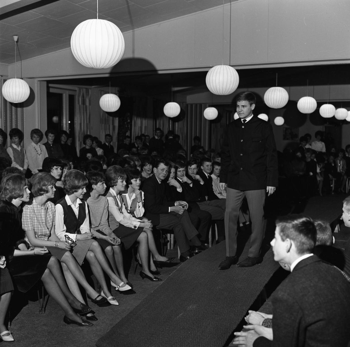 Ungdomsträff med modevisning. Jan Pettersson visar jacka och byxor. En stor publik tittar på.