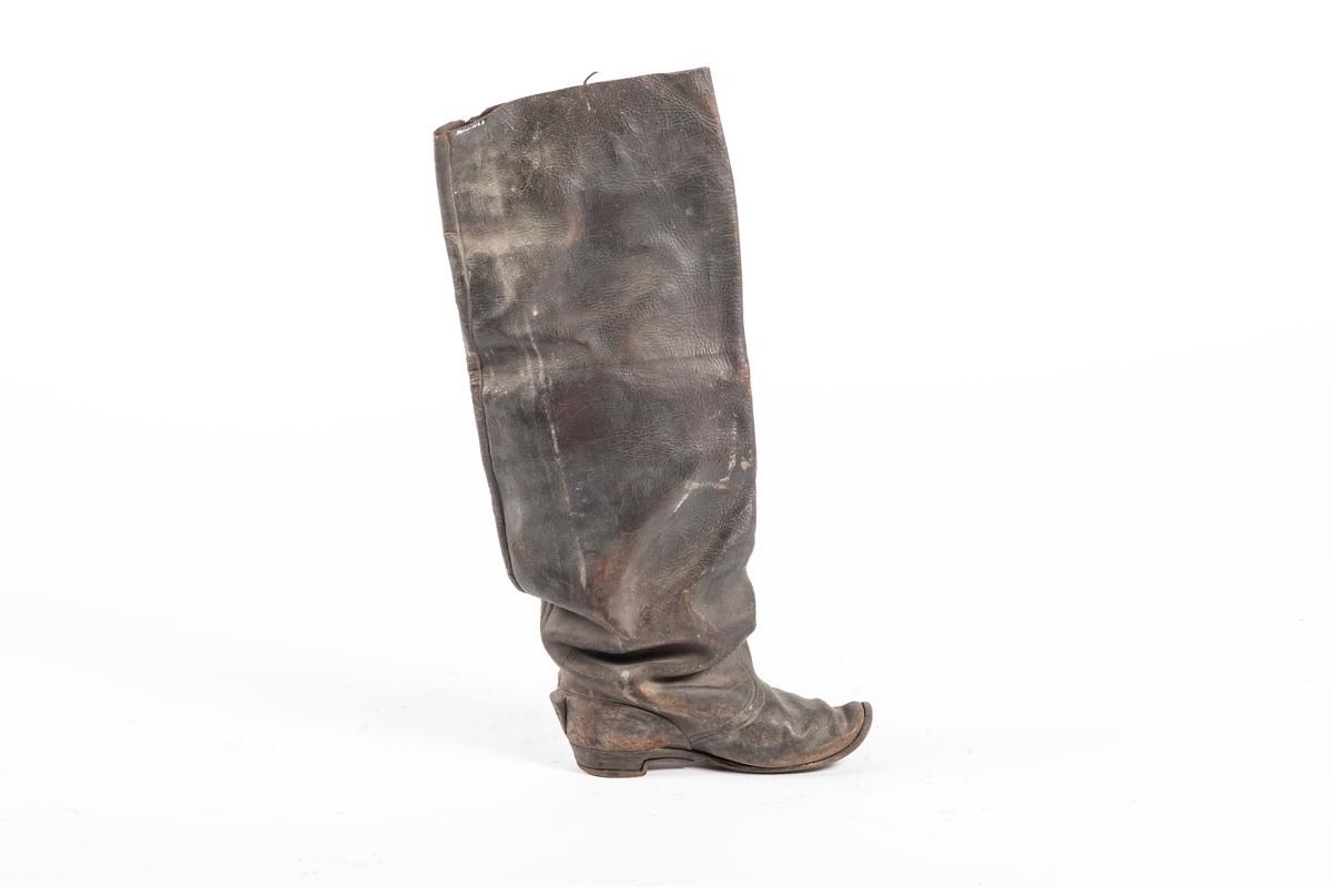 Støvlene er lange, og øverst er de vide. Sålen er av lær, og er sydd på. Tåtuppen skrår oppover. Bak på hælen er det sydd på en trekant i lær som står ut. Under hælen er sålen dekket med jern langs kanten. Øverst på den ene siden har støvlene en lærrem, som er festet på innsiden og ellers henger løst. Støvlematerialet er stivt og glatt.