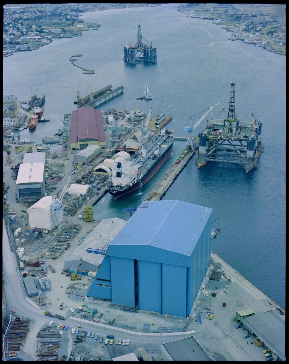 """Flyfoto av Haugesund Mekaniske Verksted med omegn. Et stort skip ligger i tørrdokken, riggen """"Ocean Liberator"""" ligger rett utenfor og en rigg ligger ved Storasundskjer. Nordsjøhallen er ferdig og tatt i bruk."""