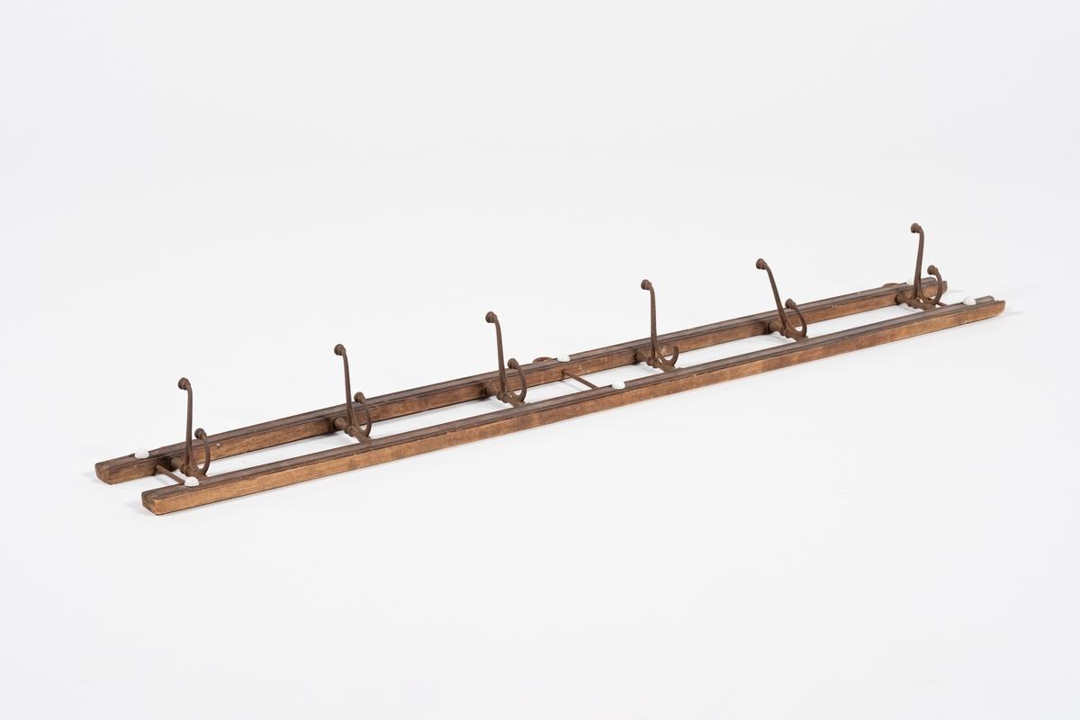 Knaggrekke som består av to profilerte lister med 6 jernknagger. Knaggene har svungne former og dekorative rander, en del av dene ene knaggen er brukket av. Knaggene er festet mellom de to listene. På hver ende og i midten av knaggrekken er det tredd gjennom en metallstang, i alt 3 stenger. Metallstengene har krok i toppen, som stikker opp gjennom den øverste lista. Ved hver metallstang er listene pyntet med to hvite knotter i porselen, i alt 6 knotter.
