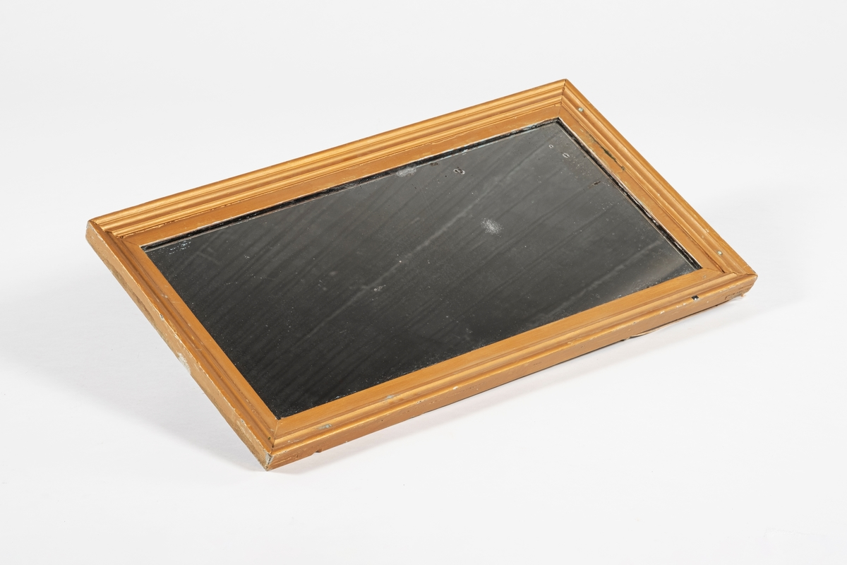 Rektangulært speil som skal henge på høykant. Ramme med flere trelister, som består av et sinket rammeverk, med profilerte lister på oversiden. De profilerte listenene er sannsynligvis limt sammen i hjørnene. På baksiden er det rester av papp. Baksiden er dekket av en metallplate, men øvre del har rustet vekk. På På øvre halvdel er det skrudd inn to kroker ved siden av metallplaten. I disse henger det taustumper for oppheng. Speilet ser ut til å ha vært malt flere ganger. Gullfargen skaller av, og det er spor etter tidligere farger som turkis, hvit og sort.