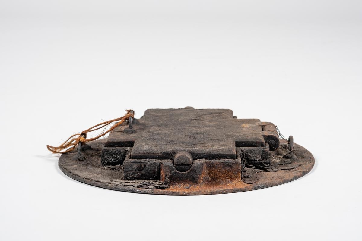 Gorojern med ring, til bruk på vedovn. Jernet er korsformet og består av to plater som ligger mot hverandre. Platene er festet i ett ledd, og på oversiden av begge platene er det et håndtak. Dette gjør at jernet kan brukes på begge sider. Gorojernet ligger på en rund jernplate. I jernplaten er det stanset ut en korsform som gorojernet passer over, og det er kanter som holder jernet hevet. Jernplaten har håndtak på to sider, slik at det kan løftes på og av vedovnen. Gorojernet kan i dag ikke løftes av jernplaten, det er festet med ståltråd fra leddet og til håndtaket i jernet.