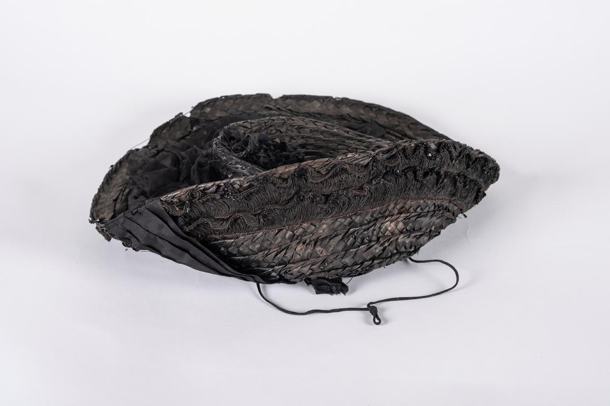 Svart, flettet stråhatt med pyntebånd på oversiden av bremmen, som går rundt kanten og på undersiden. I hver ende av pyntebåndet er det en sløyfe. Ved pyntebåndet på bremmen er det også en blomst laget av tyll. Oversiden av pullen er dekorert med en blomst, laget av ståltråd dekket med tekstil. Undersiden av bremmen har to pyntebånd av tråd og paljetter. Svettebånd av bomull.  I halve pullen innvendig, mellom svettebånd og pull, er det et forsterkningsbånd av fløyel. I fòret er det festet en hakesnor.