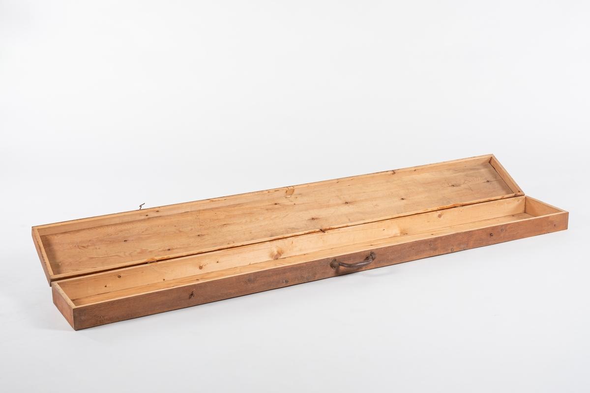 Rektangulær lang kasse til oppbevaring av fane. Den består av bunn og lokk som er henglet på. Kassen lukkes med to kroker og har et jernhåndtak.