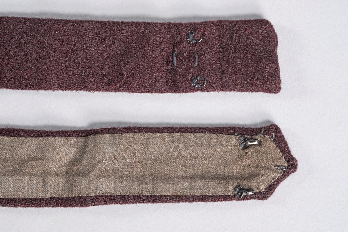 Lilla belte i ulll som hører til todelt drakt. Det er sydd på tre metallhekter i den ene enden. Et hekte er festet på innsiden av foret, og to stykker i bredden nedenfor. Disse to hektene er sannsynligvis festet i etterkant da de er sydd fast i foret. For feste av beltet er det sydd fast to små metallhemper i andre enden av beltet, samt to tekstilhemper. Tekstilhempene er nok for feste av den originale hekten. Beltet er foret på innsiden.