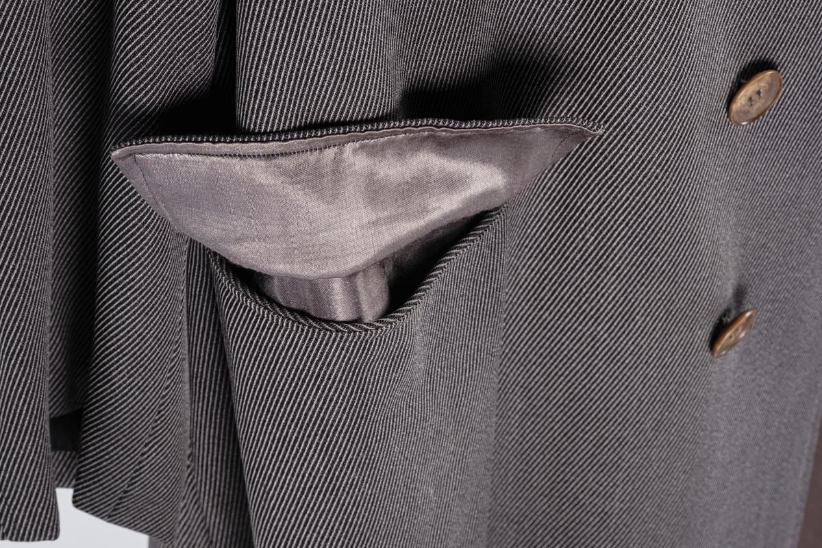 Rett frakk med slag og raglanerme. Foring av silke. Skjult knepping med fire knapper, kan også kneppe slaget under kragen. To lommer med klaff og to innerlommer. Splitt bak med knepping. Spensel nederst på ermene.