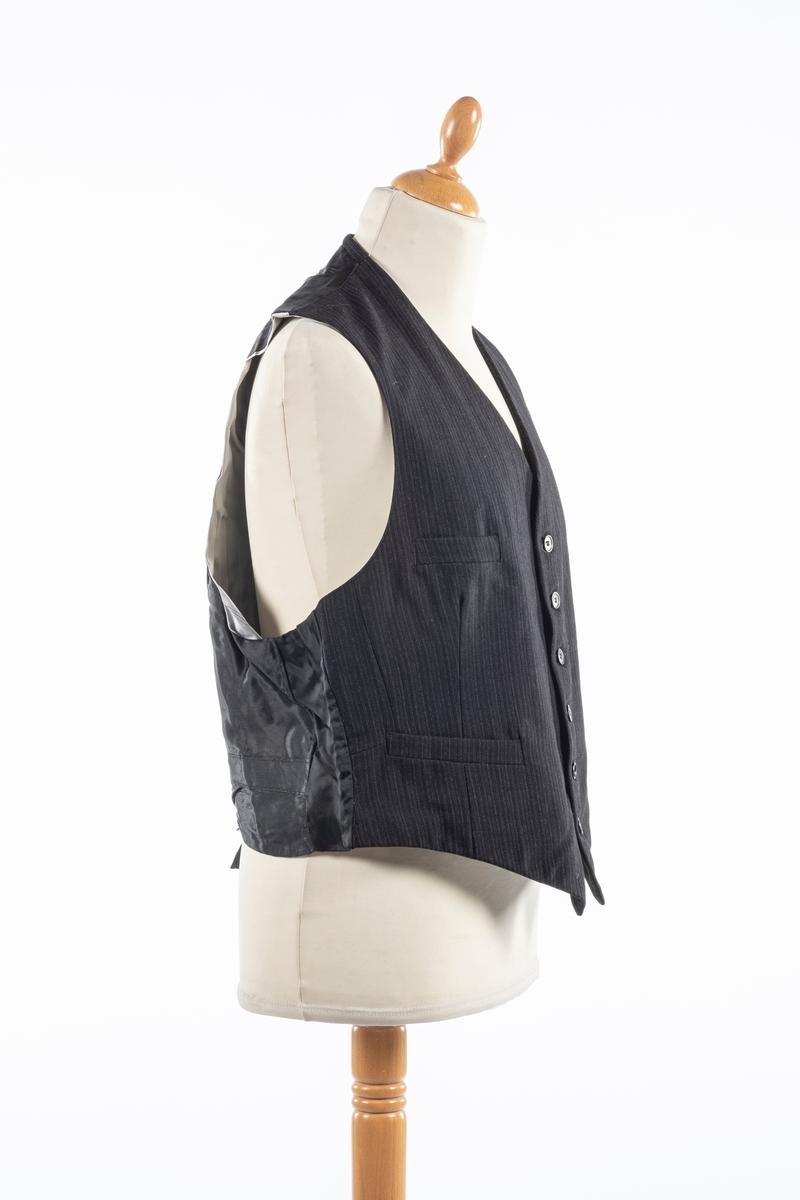 Vest med forstykke i svart stripete ullstoff og bakstykke i svart silke. Den har foring i stripete stoff. Den lukkes i front med seks knapper og har spensel i ryggen. Vesten har fire forlommer.