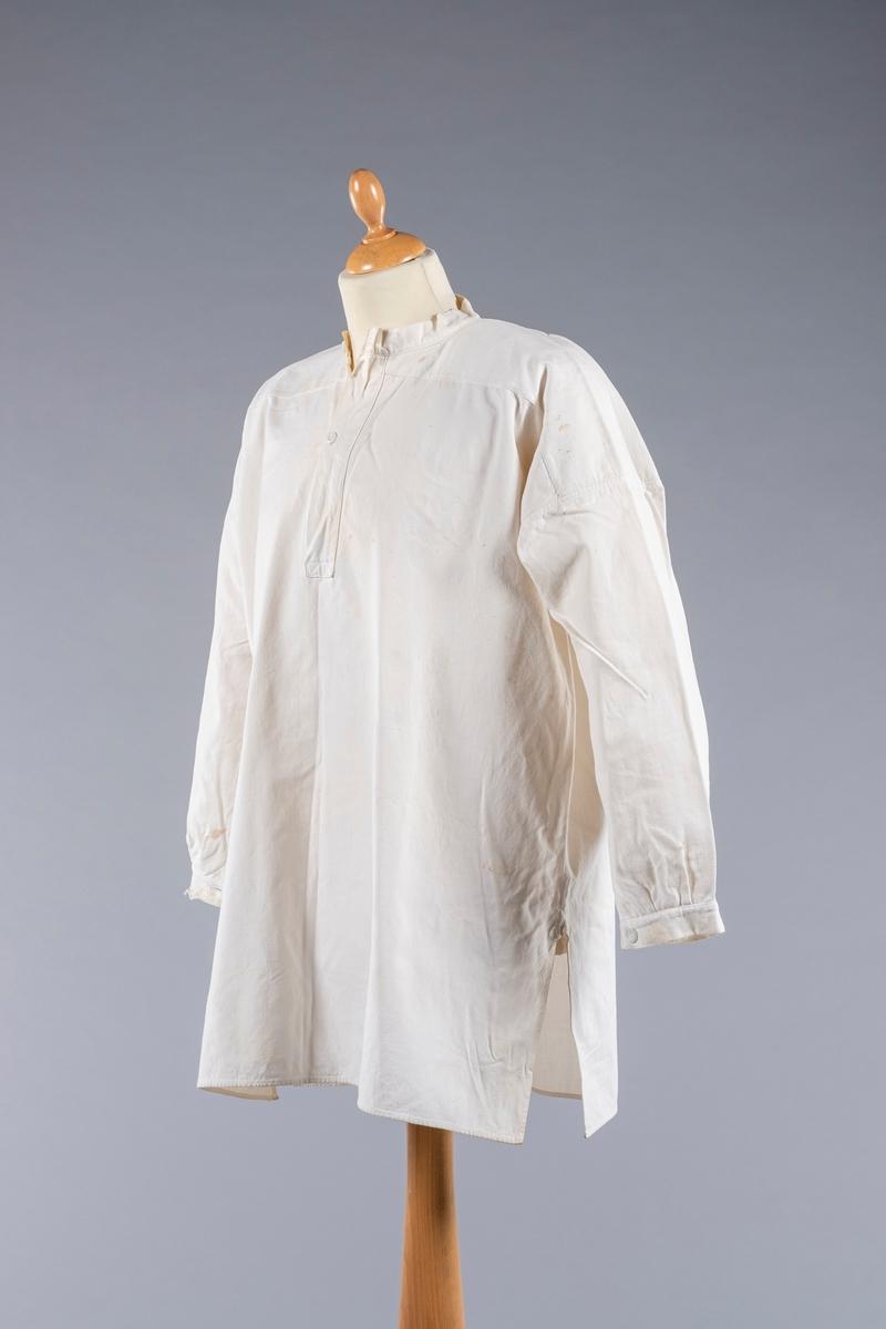Skjorte i hvit tykk bomullslerret. Bolen er sydd glatt til bærestykket. Halsåpningen har splitt foran og åpning på 25 cm. Den lukkes med 2 knapper. Isydde ermer med kile. Ermene har smale mansjetter med mansjettknapper. Det er splitt i hver side nederst. Skulderstykket er dobbelt.