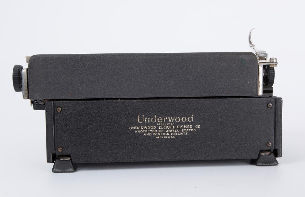 Standard reiseskrivemaskin m/rull og blekkbånd. Maskinen er festet i en kuffert, lokket løftes opp v/bruk. Bærehåndtak. Runde tastaturknotter i fronten m/tall og bokstaver. Fabrikkprodusert.