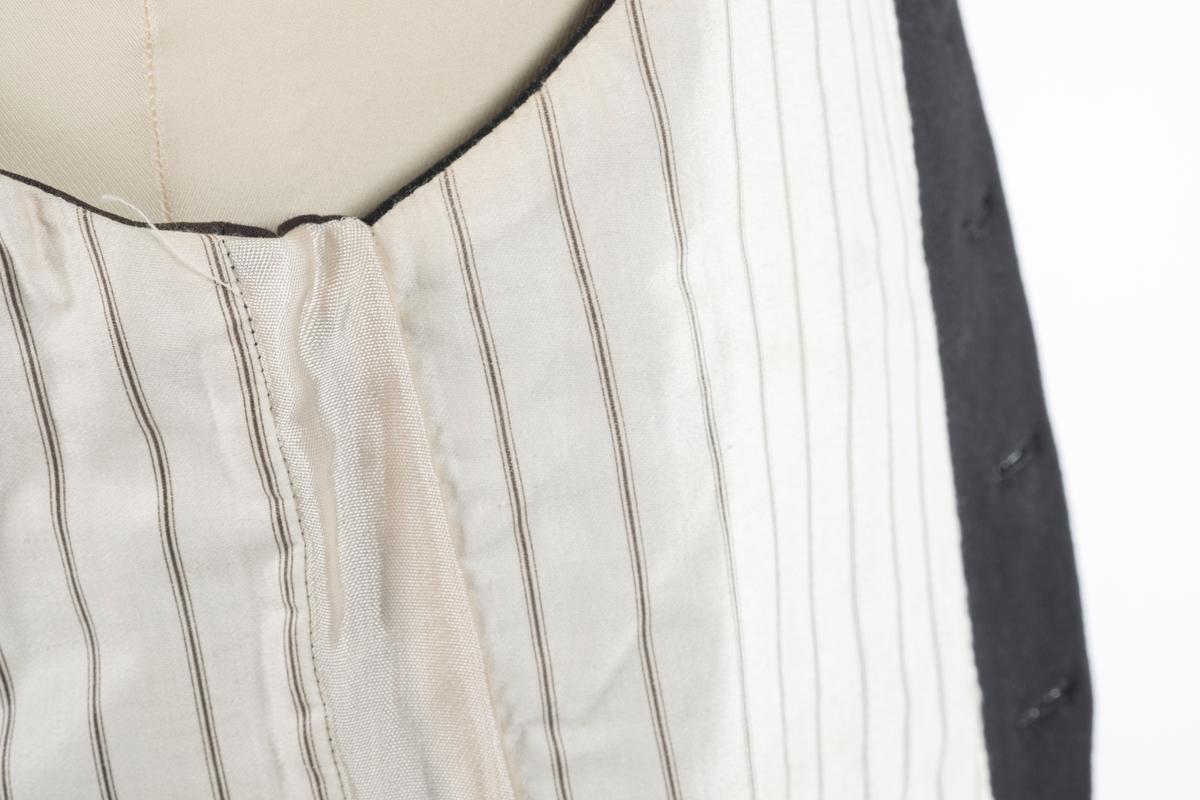Svart vest med krage og tre lommer i front. Ryggen er i bomullstoff. Det er spensel i ryggen. Vesten er foret med hvit bomullstoff med sorte striper. Vesten kneppes med 6 knapper.