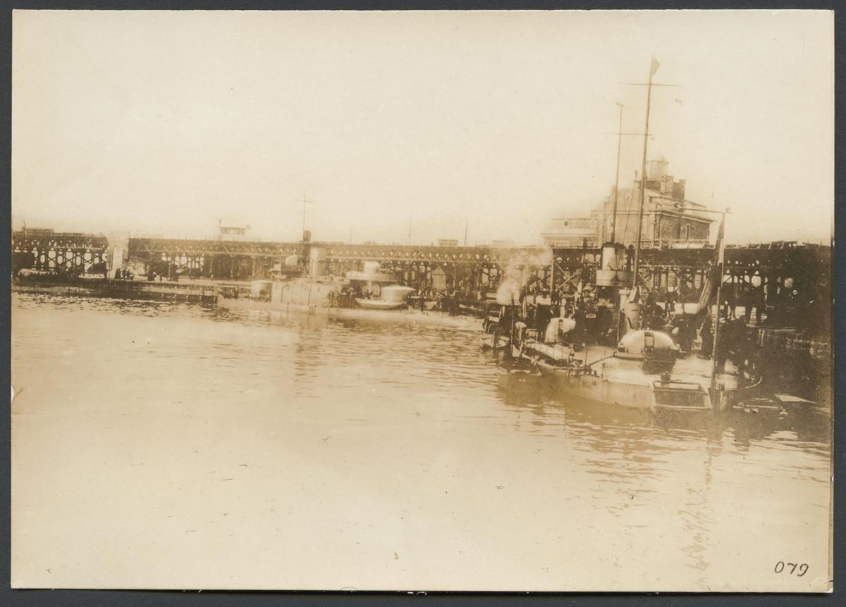 """Bilden visar hamnbassängen i Odessa med ett flertal örlogsskepp som ligger förtöjda vid kajen. I bakgrunden syns en stor träbro.  Originaltext: """"Krigsskepp, tillhörande K. K. Donau-flottiljen i Odessas hamn."""""""