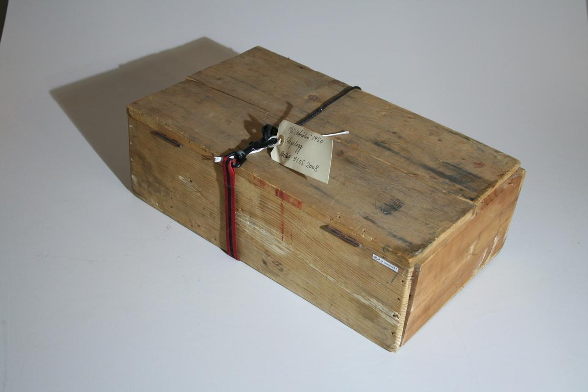 Retangulær trekasse med lokk som sitter fast med to hengsler. Lokket er ødelagt, delt i to, der den ytterste delen ligger løst på kassen. Lokket skal lukkes med to kroker. Kassen er delt inn i 5 rom med to gjenstander. Telleverk på sokkel, øyebolt og med et fastspleiset tau rundt sokkelen. Telleverket viser en stor skala fra 0 - 100 og en liten skala fra 0-9 med en liten viser. Tauet er ca.146 cm langt.  En rotator med line. Det sitter litt papir fastlimt øverst på rotatoren.