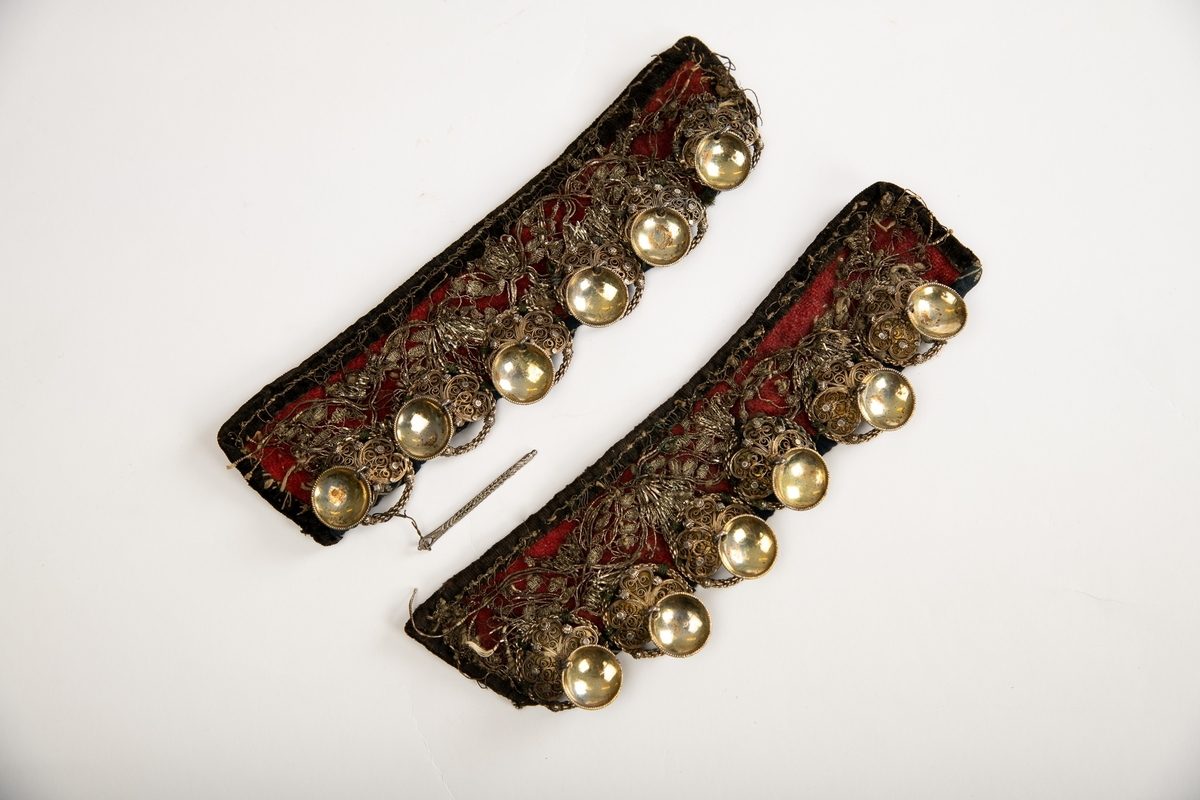 Hvert forstykke er et smalt, rektangulært stykke  rødt   ullstoff,  kantet med sort fløyel og besatt med  sølvblonder. Den ene side har 6 par sølvmaljer i forgylt  filigransarbeide, hver malje har, 1 løv. Til høyre forstykke  er festet en  tilhørende lissenål(av sølv?). Forstykkene er foret på baksiden med  strie.