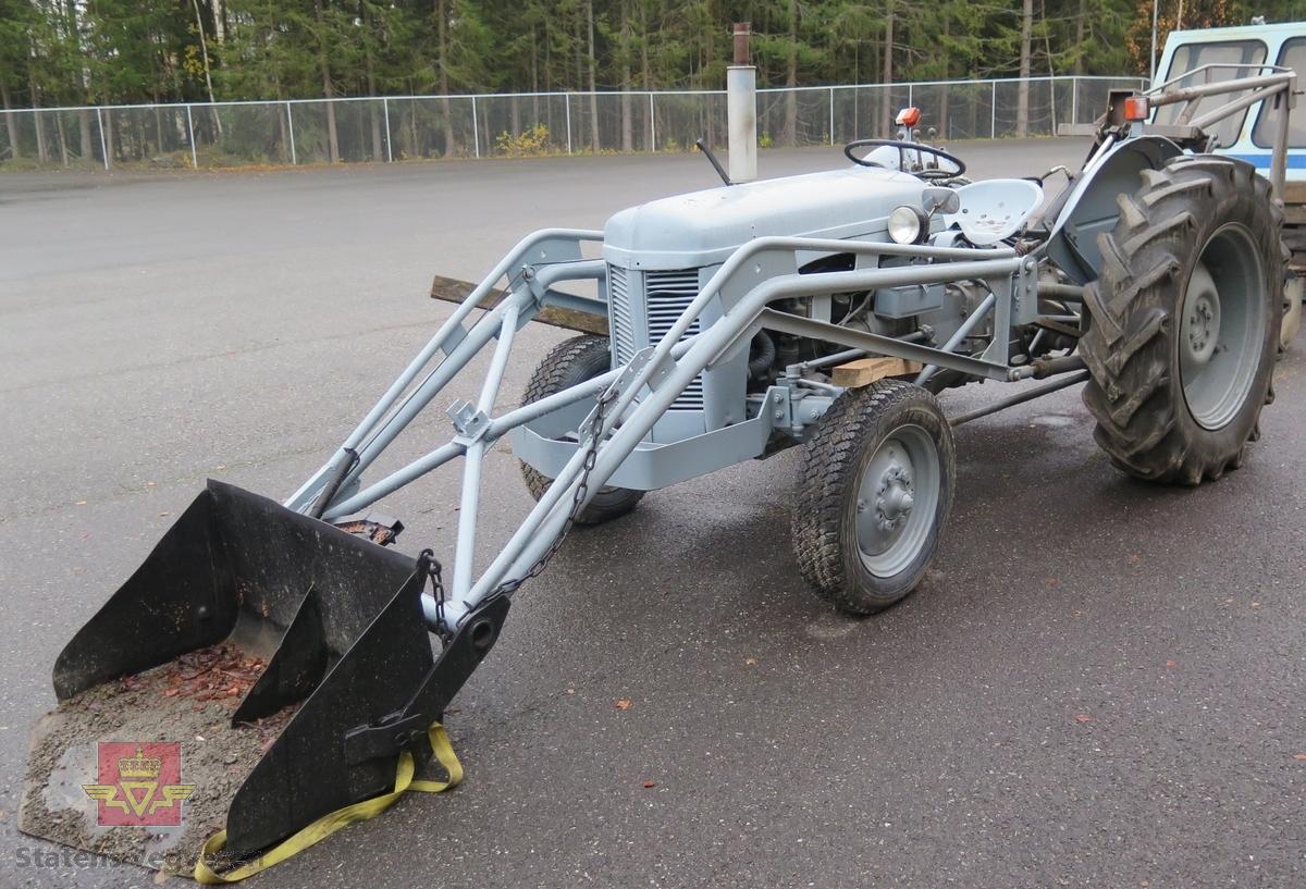 Grå traktor med lasteapparat foran og graveaggregat bak. Motoren er en 4-sylindret bensinmotor fra Standard Motor Company.
