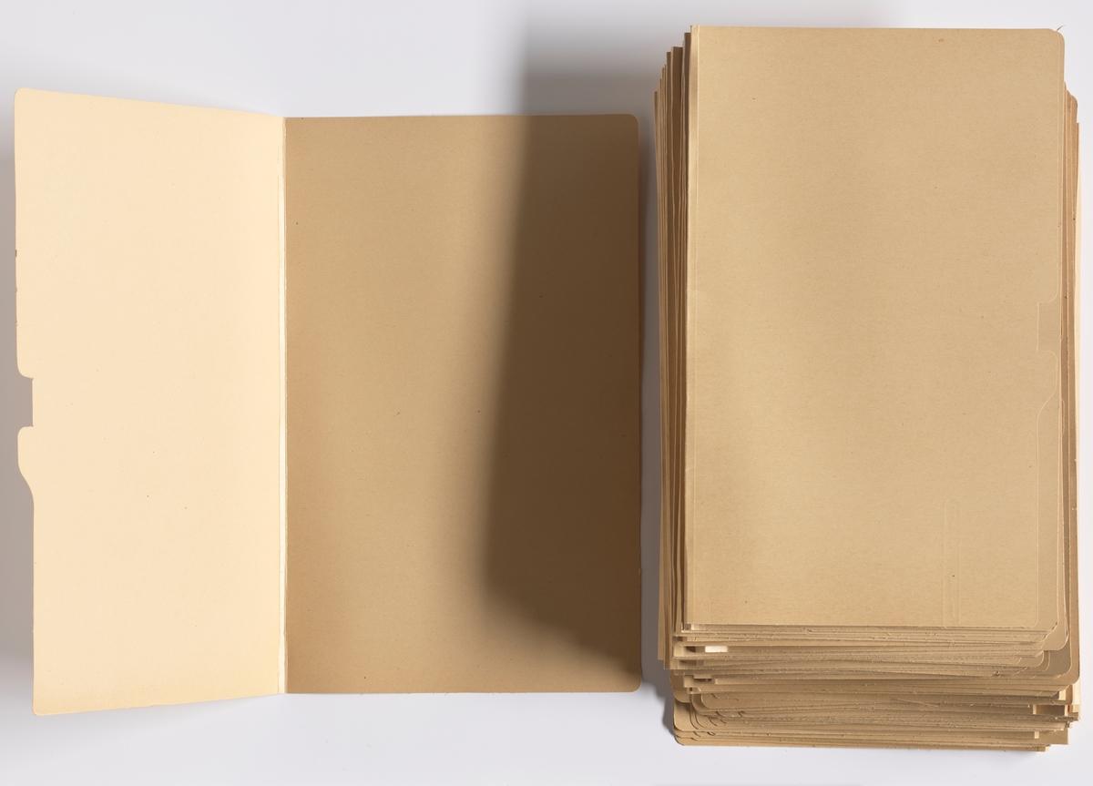 Mappe i papp til å oppbevare dokumenter. Mappen kan åpnes øverst for å legge i dokumenter. Øverst på fremsiden av mappen er kanten formet for å feste den til en mappeholder. Det er totalt 50 mapper.  NAV-samlingen er en gruppe av gjenstander som har vært anvendt på sosialkontoret (Aetat - NAV) i Skedsmo kommune.