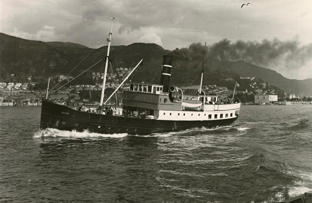 Motivet viser DS OSTER (bygget 1908) på vei ut fra Bergen havn med Sandviken til venstre og Bontelabo til høyre i motivet.