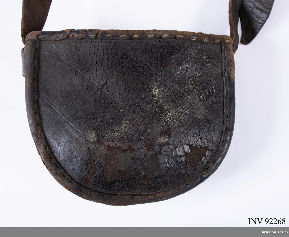 Halvcirkelformad väska utan lock. Möjligen för hästskor. Dekorerad på sidorna med inristat rutmönser. Kraftig rem.