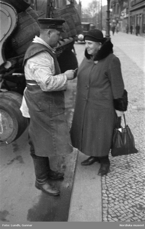 """Motiv: Tyskland, Berlin; Porträtt av en man """"Tiller"""" som dricker ur ett glas.  Motiv: Tyskland, Berlin; Utsikt från ett restaurangfönster över ett torg med torghandel, en man står vid ett försäljningsstånd med skylt """"Sie husten nicht mehr!....."""", gatuvy med en cyklist och en bil, gatuvy med bilar och en man som skjuter en kärra med text """"G. Pabst Lack-Fabrik"""", skylt """"Diese Villen sind im ganzen oder geteilt zu vermieten....."""", grind med skyltar """"Prof. Georg Klempener"""" """"Professor Dr. A. Pinkuss"""", gatuvy med an man som samtalar med en kvinna, ett bord på gatan med böcker till försäljning, skylt """"5 zimmer wohnung 1 etage auch geteilt per 1. april näheres b. wirt."""", exteriör av byggnad med stor skylt på fasaden """"Zu vermieten...."""", gatuvy med bilar - spårvagn - man med handkärra och en man som sopar gatan."""
