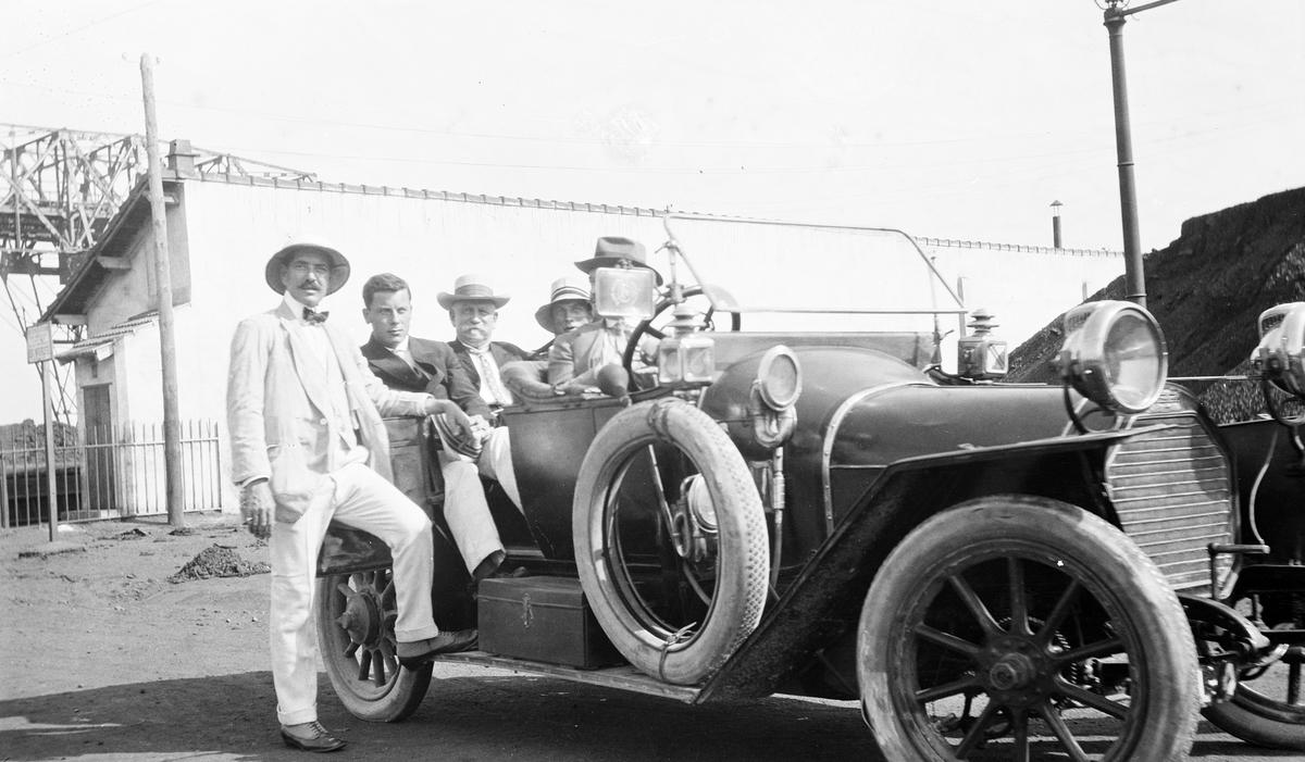 Åpen bil (den samme som ble fraktet med D/S STORFOND) på land. Bak i bilen sitter kaptein Gustav Waage mellom sønnene sine. Motivet er tatt i et havneområde.