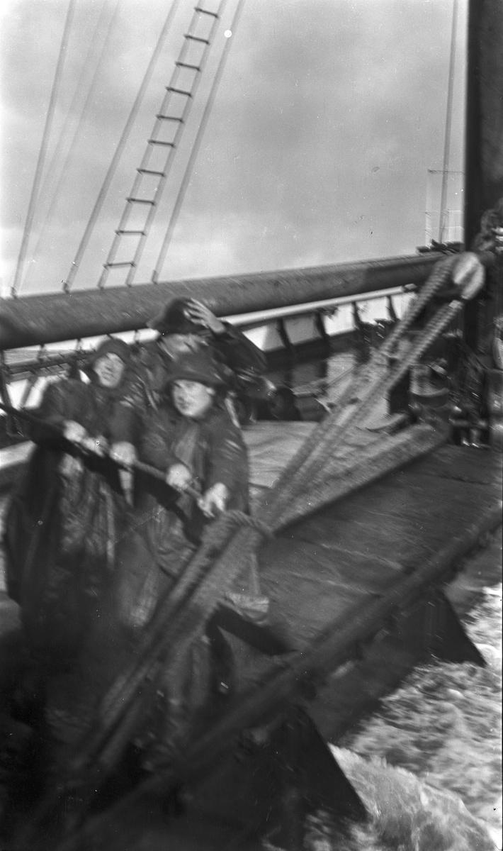 Tre menn i oljehyre haler i reip om bord på DS STORFOND. Brottsjø skyller over dekk.