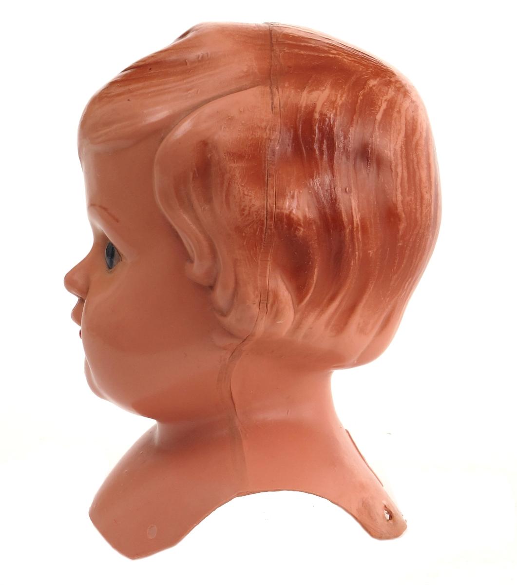 Dukkehode i celluloid. Øyer av innstøpt plast (?). Malte detaljer munn, øyebryn og,hår.  Hull i skulderpartiet for påsying av dukkekropp av tekstilt materiale.