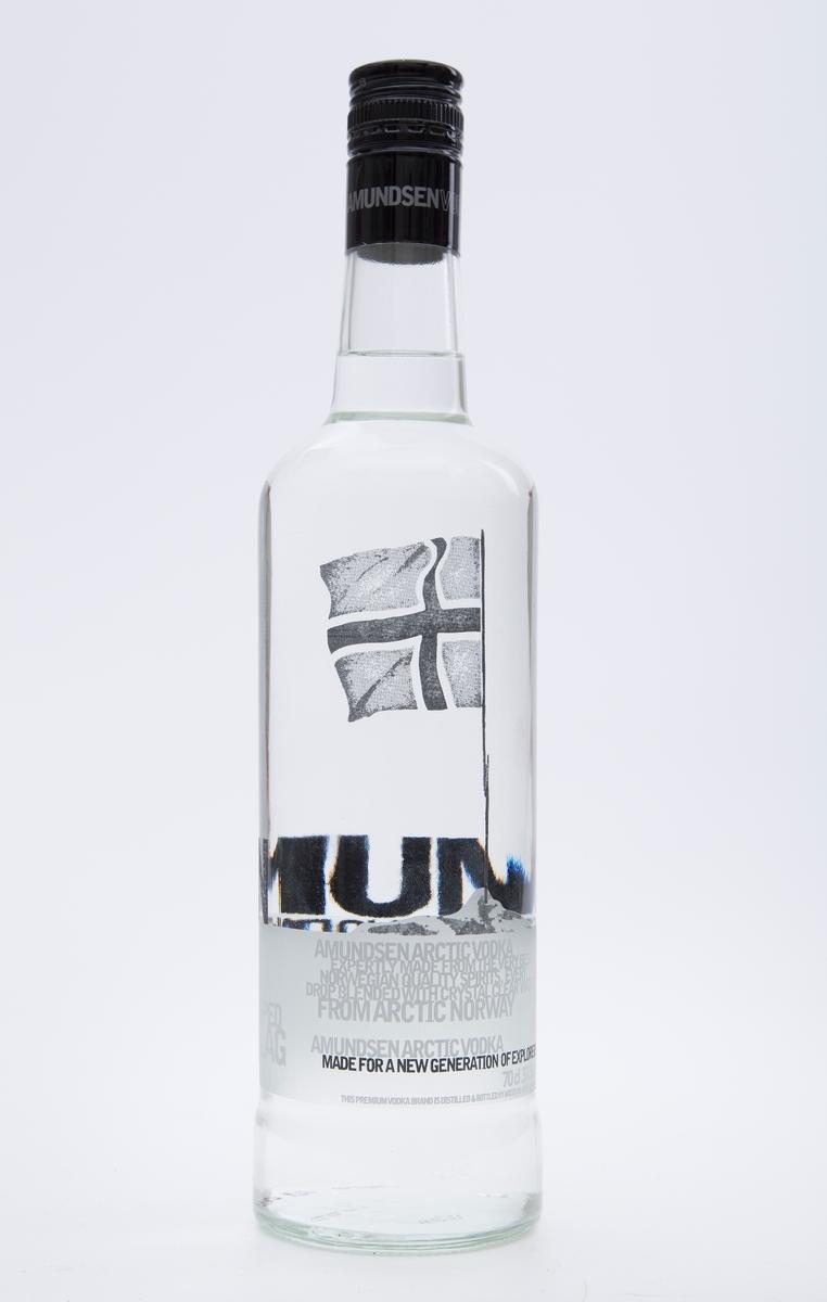 Flaske. Brennevinsflaske, klart glass med hvit og sort skrift, sort metall skrulokk med sølvskrift. Plombering ubrutt. Mrk. Amundsen Arctic Vodka. Fabrikkprodusert av Arcus A/S - Norge.