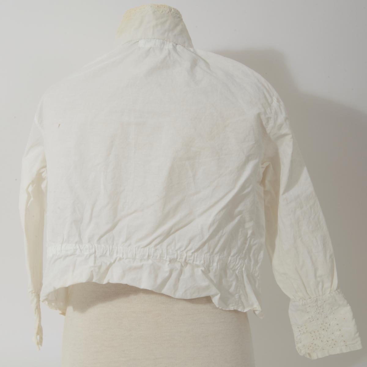 Krage og mansjetter er påsatt en sydd bluse som har smal blondekant i hals og rundt håndledd. Mansjettene er tatt fra annet broderi og satt sammen av 2 deler. Skjorten har 3 sølvknapper.