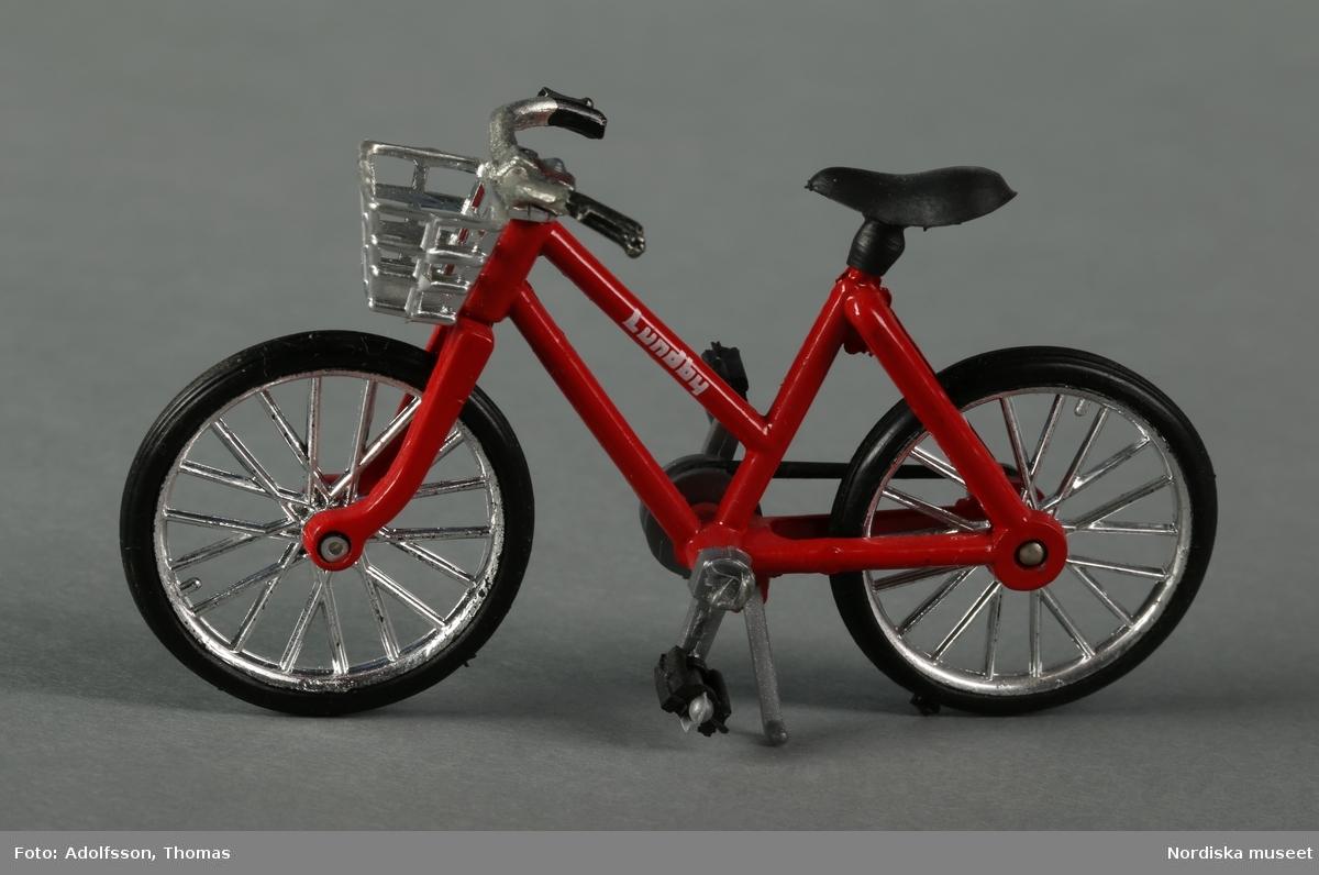 """En röd flickcykel märkt """"Lundby"""". Den rödmålade stommen är av metall, medan sadel, hjul, cykelkorg, pedaler, kedja, handtag mm är av plast. Pedalerna, hjulen och stödet är rörliga. Cykeln hör till dockskåpsinredningen i garaget i källarvåningen i dockskåp NM.0331721+."""