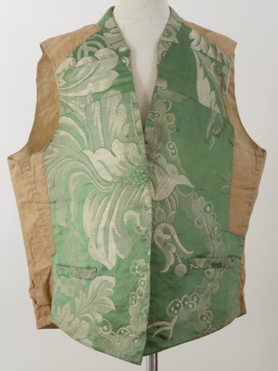 Grønn og hvit med sort mønster, forkant buet med 4 knapphull, nede 2 stikklommer, bakside og for ubleket/bleket lerret, vattert foran.