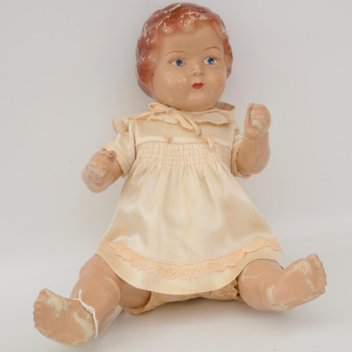 Støpt dukke med løst hode, armer og ben. Er fra den tidlige produksjonen, da de blandet pimpestein og Casco-lim med vann og helte i fomer. Ble så spraymalt med kropps- og hårfarge. Håndmalt ansikt. Ble solgt uten klær.  Dukkeklær hjemmesydd: kjole, kyse og truse i tykk silke, trøye i tynn silke m/blonde.