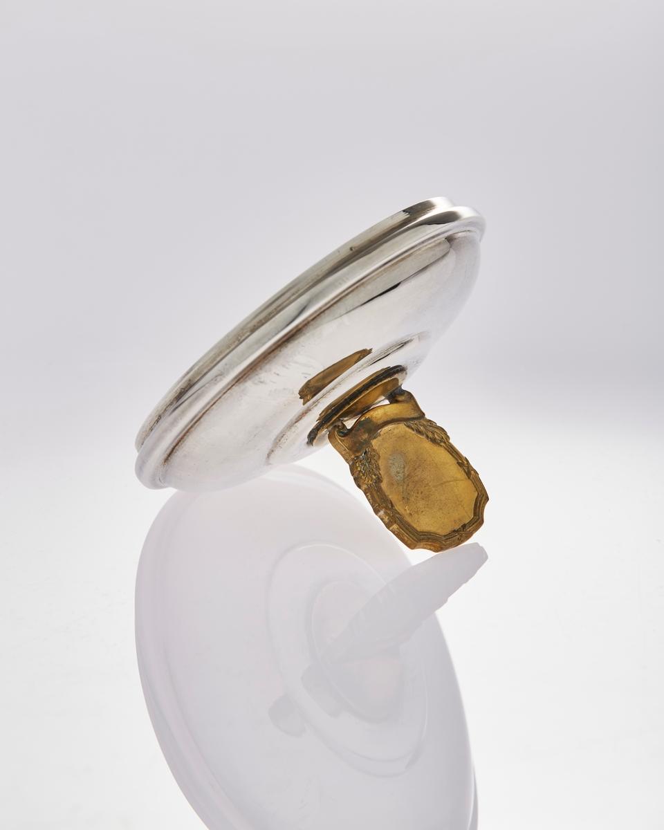 Lokk til pokal i sølvplett med messingemblem på toppen. Det har trolig sittet et merke inni emblemet.