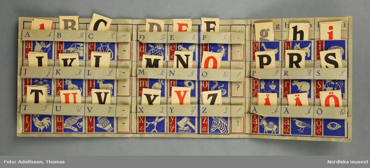 """Pedagogiskt läromedel i form av mapp med lösa bokstäver. Mappen förvaras i ett kuvert. a) Mapp av brunt papper. Rektangulär form vikt till en kvadrat. De olika papperslagren är ihopsydda på symanskin. Tryckt text på fram och baksida. Inuti mappen 33 fickor med bilder. I fickorna b+) lösa rektangulära papperslappar med bokstäver och räknetecken.  Mappen ligger i c) ett kuvert av brunt papper. Tryck på fram- och baksidan. På framsidan text samt bild med två barn vid bord och bokstäver. På baksidan text med historia om """"bokstavsfolket"""". Anm. kuvertet något nött och lite trasigt i hörnen. / C Hammarlund-Larsson 2019"""