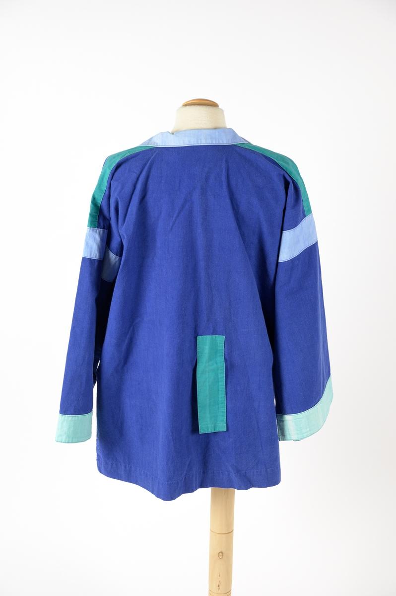 Skjorta designad av Barbro Sörman för Twilfit. Skjortan är kornblå med detaljer på ärmar, fickor och krage i ljusblått och mintgrön 100% bomull. Vid modell som dras över huvudet, krage och slag samt att det är sprund på båda sidor, två stora utanpåliggande fickor nedtill, dessa har en kant av ljusblått tyg. Gröna klaffar och ljusblå kilar vid ärmen, mintgrön bård vid ärmslut. Baktill sitter en grön rektangulär detalj som ev. sytts dit i efterhand för hand och den täcker ett litet hål. Skjortan har några fläckar på framsidan samt att den troligtvis är något blekt.