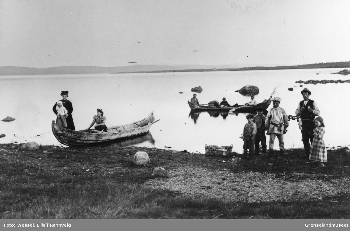 Pasvikelva ved Svanvik/Salmijärvi i 1890-årene. En båt ligger ved elvebredden med to kvinner og et barn i. En båt ligger ute på elva med tre menn ombord. Fire barn og en mann står på elvebredden.