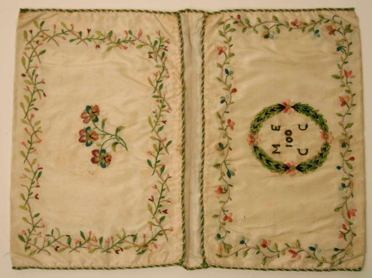 Plånbok i siden. Från Falun.  Vänster yttersida med två fåglar som näbbas inuti en ram av blomsterslingor. Höger yttersida blomster i kruka samt blomstermotiv inom ram av blomsterslingor. Vänster innersida pensémotiv inom ram av blomsterslingor. Höger innersida bokstäverna: M E - 100 - C C, inom en tät fyrdelad krans alltsammans inom en ram av blomsterslingor. Plånbokens kanter tränade med silkessnodd. Initialerna sydda med människohår. Vitt sidenfoder.  Gåva av fröken Th Brandberg. Tillhört rektorn vid trivialskolan J E Brandberg.