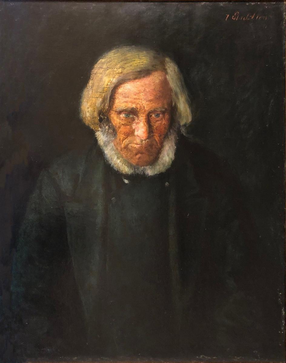 Portrett av eldre mann med grått hår, skjegg og mørke klær.
