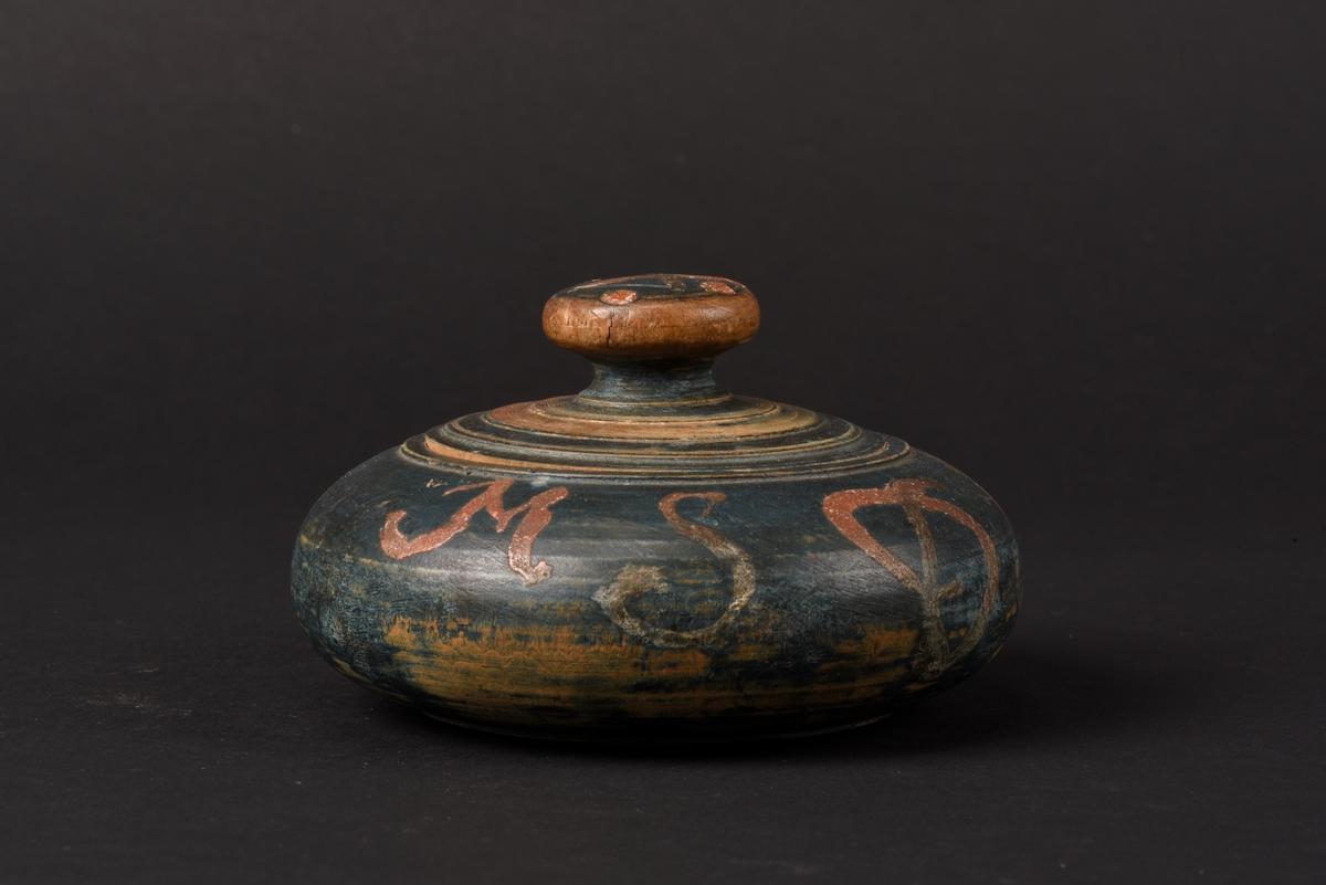 Rund svarvad smörask med lock, tillverkad av trä. Locket har ett runt svarvat knopphandtag. Asken är målad i blågrönt och försett med initaialer, MSD, och årtal, 1804, i rött. På knoppen ett ditmålat kryss och fyra punkter.