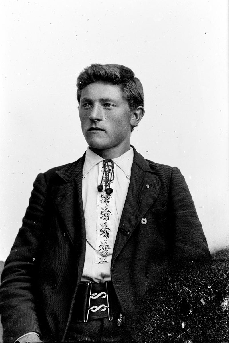 """Studioportrett, ung mann, med brodert skjorte, """"lisse"""", lissebinding i halsen, mørk jakke, bredt belte med to S'hekter. Svensk?"""