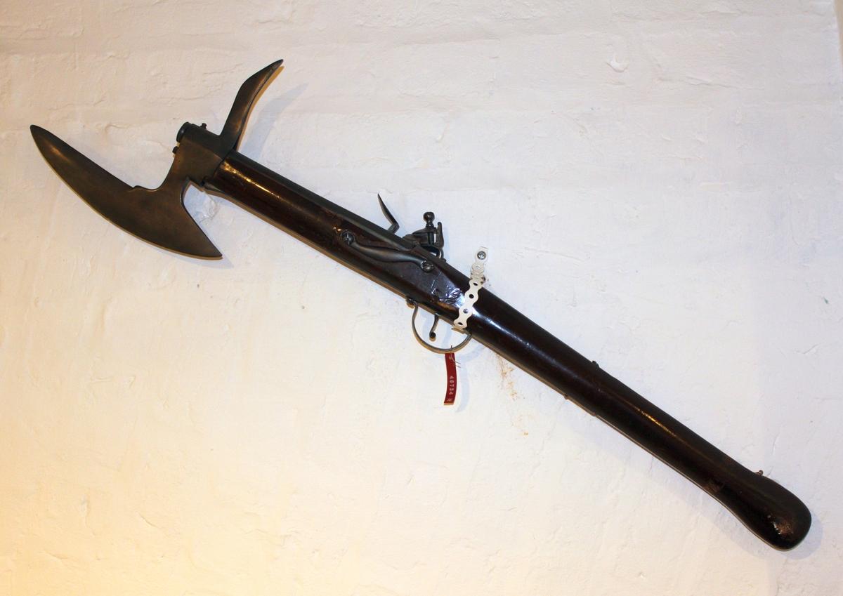 Gjenstanden er en karabin med flintlås av Dpg-lock-typen med stridsøks og entreigg, såkalt tre-i-ett-våpen. Fremstillet i tre og stål. Låsblikket stemlet. Stemplets mål: 2,9 x 2,2 cm. Løpets venstre side stemplet. Stemplets mål: 3,5 x 3,0 mm. Venstre side av øksebladet stemplet.  Stemplets mål: 3,5 x 2,5 mm. Opprinnelig registrert som tyrkisk våpen. Tysk produksjon iflg. henvisningene. Stemplingen på løp og økseblad er arabiske skrifttegn.