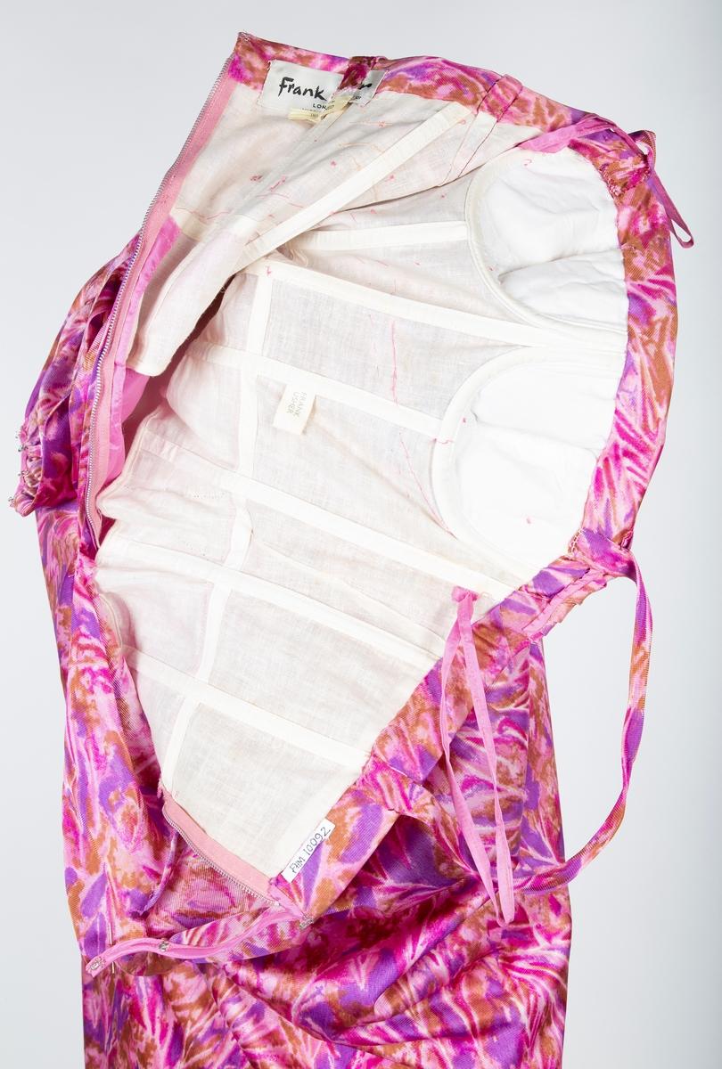 """Selskapskjole, lang, syntetisk, trikotvevet stoff, lilla, rosa og bronse.  Underliv med brystholder sydd i fast linstoff, 9 stående korsettspiler, buede spiler under bysten. Rosa forsilke i skjørtet..  Det mønstrede trikotstoffet er drapert rundt livet og bysten, Smale skulderstropper, Metall glidelås  Konfeksjon. Mrk:""""Frank Usher/ London"""". Str.38  Innkjøpt til venninnes bryllup. Giver Astri Breder Berg"""