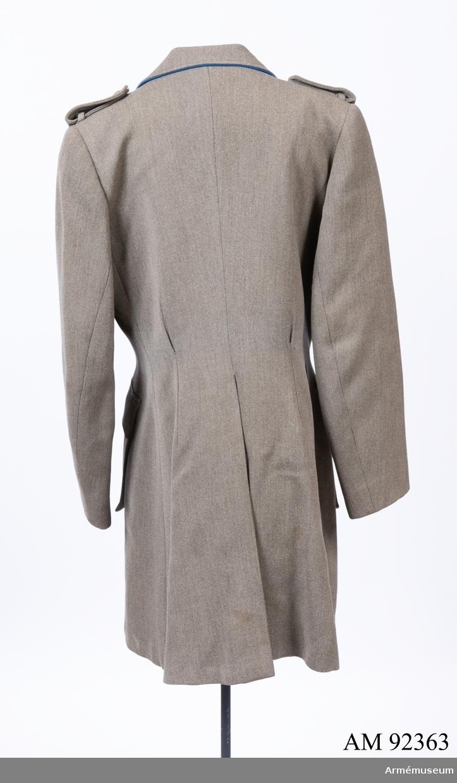 Jacka sydd i grå yllediagonal med märken och knappar för Svenska Blå Stjärnan samt blå passpoal kring kragen. Ovanför höger bröstficka ett märke för genomgången kurs i hästsjukvård.