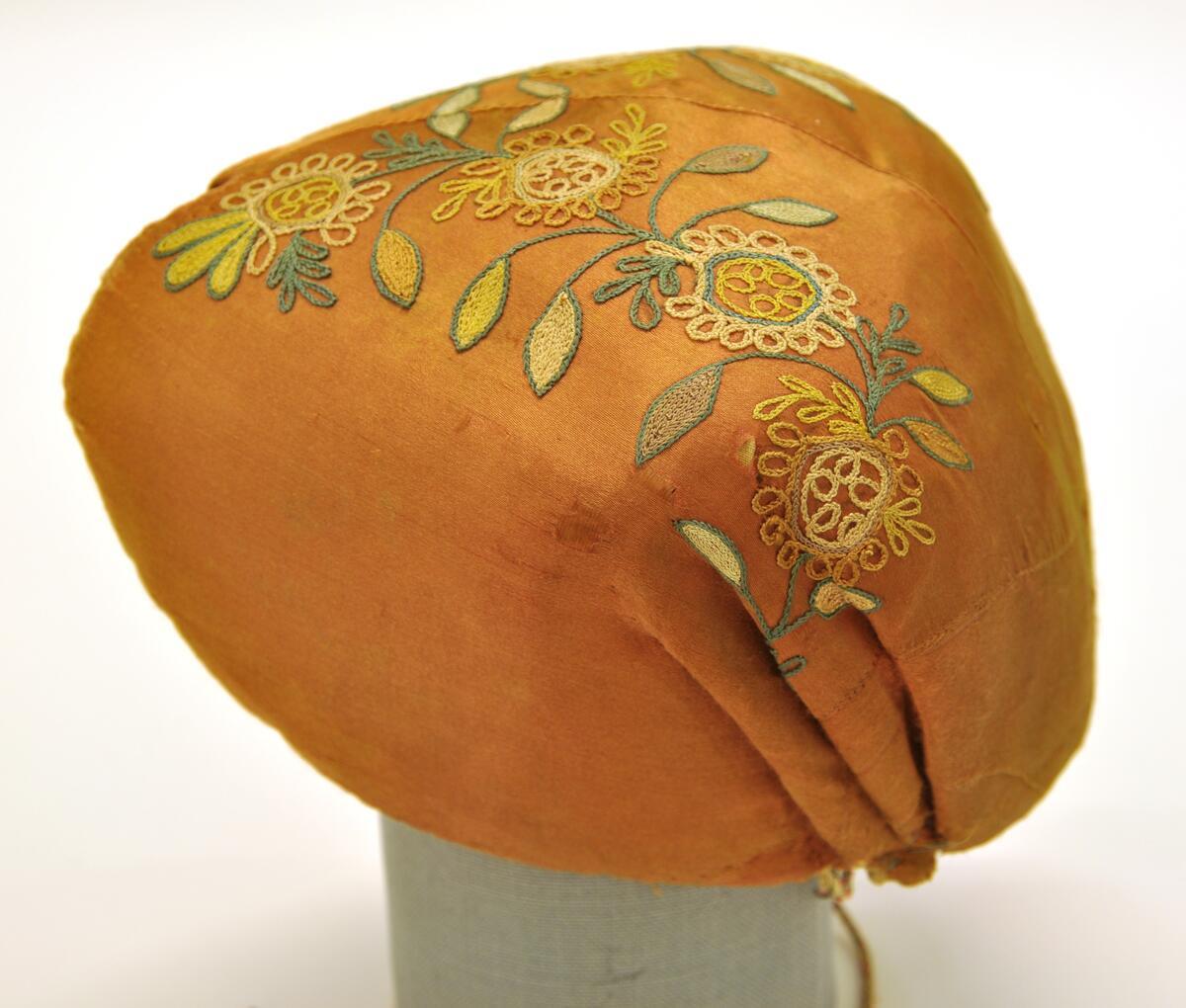Bindmössa från Lyckegården, Toarps sn, Ås hd. Enligt uppgift brudmössa. Orange sidensatin med broderat blommönster i gult, blågrönt, naturfärgat, beige och orange silke. Hjärtformat urtag mitt fram, framkanten kantad med orange sidenband. Mittsöm, sammanfogad av mindre tygbitar baktill. 3 veck i var sida. Tvinnade knytband i rött, grönt och ofärgat. Fodrad med ofärgat linnetyg, kypert.