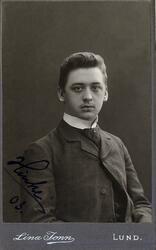 Porträttfoto av en man i kavajkostym med väst, stärkkrage oc