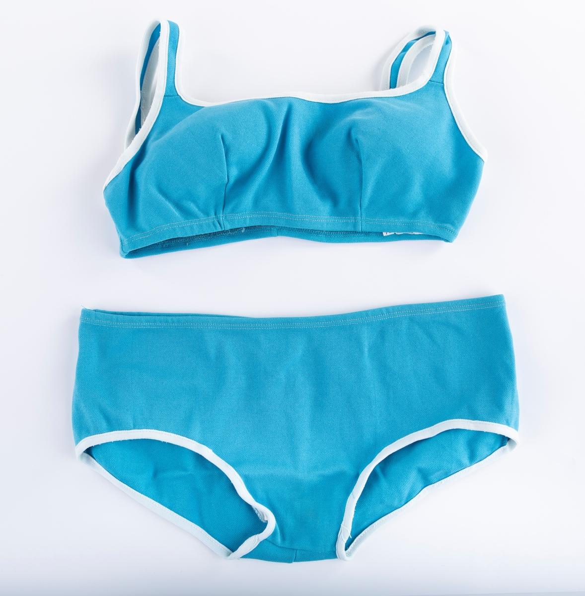 Bikini A: Bukse  Truse. Turkis. Hvite kanter ved bene. B: Overdel Hvite bånd rundt armer og skulderstropper og over brystpartiet. Innlegg av plast i brystpartiet.  Kjøpt hos Eivind Jensen, Drammen.