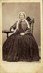 Porträttfoto av en medelålders kvinna i krinolin med jacka o