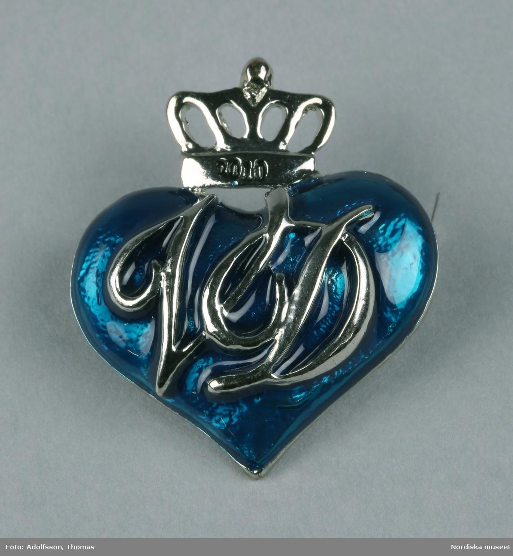 """Brosch av vitmetall i form av blått hjärta med sluten krona ovantill. På kronan text """"2010"""" coh på hjärtat """"VD"""", vilket står för Viktoria och Daniel. På baksidan nål.  /Leif Wallin 2010-09-10"""